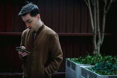 male in brown jacket looking down at his phone